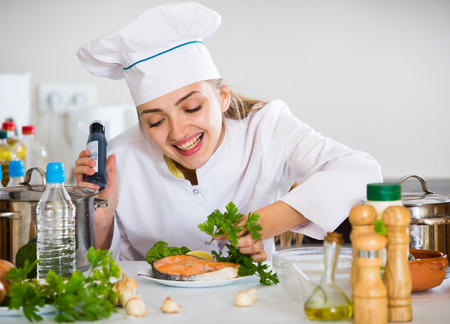 freshwater fish: Positive female chef posing with trout fillet in kitchen