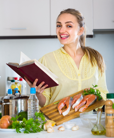 jorobado: Cheerful smiling girl cooking rainbow trout at new recipe in book