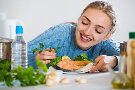 jorobado: Smiling girl in blue sweater with prepared salmon at kitchen