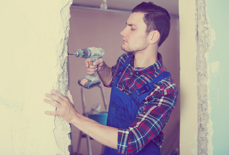 Professional builder drilling hole in wall with perforator