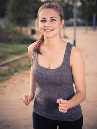 Young spanish positive female in sportwear running in the sunny park