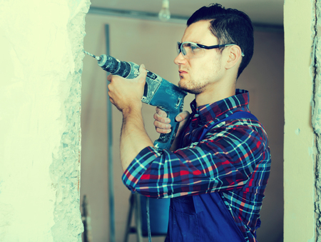 adjuster: Portrait of builder handyman with electric drill indoors