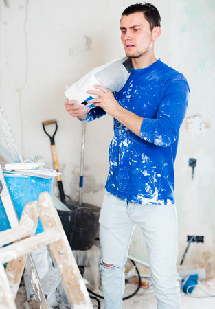adjuster: Young worker standing with bag of putty in hands in repairable room