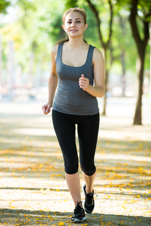 Young happy british female in sportwear running in the sunny park Stock Photo