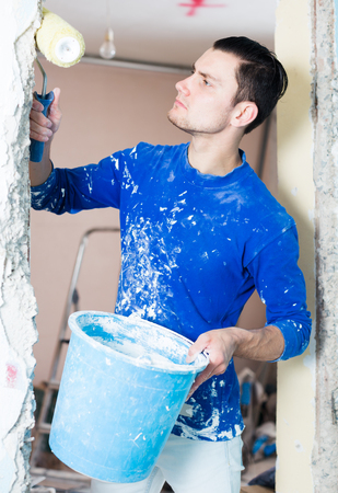 grounding: Male construction worker priming and painting doorway with painting roller