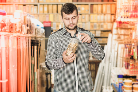 Handsome male customer examining various DIY details in houseware store Stock Photo