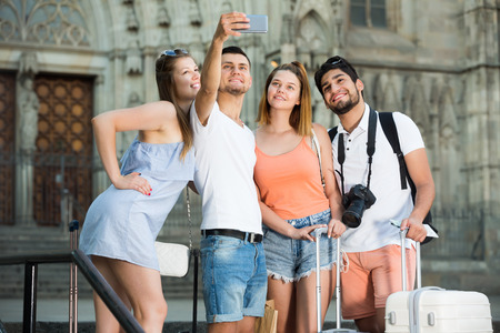 carrying: Four young travellers smiling and making selfie with mobile phone Stock Photo