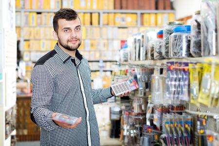 Happy male customer examining various DIY details in houseware store