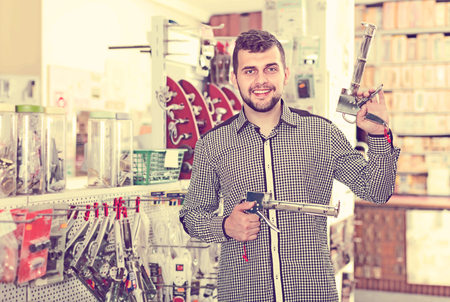 durable: cheerful male customer examining various glue guns in houseware store