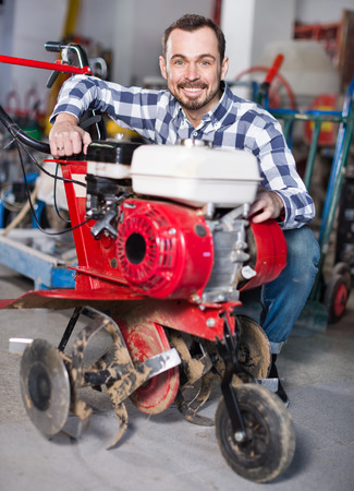 Young happy smiling guy gas plow for work at a workshop Stock Photo