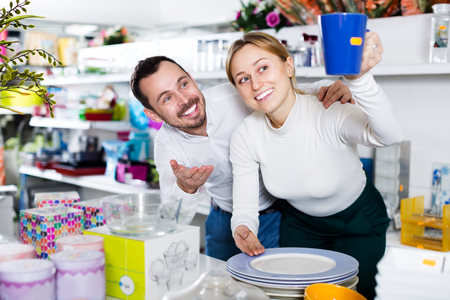 Young positive couple deciding on best crockery in dinnerware shop
