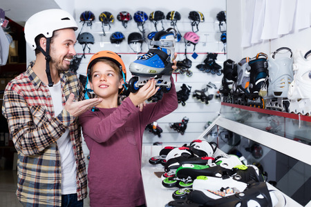 Smiling guy with dad are looking on the newest roller-skates in store. Stock Photo