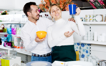 acquiring: Adult glad couple choosing new crockery in dinnerware store Stock Photo