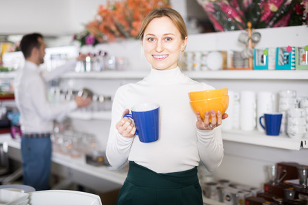 Young woman demonstrating the selected dishes in a ceramic shop