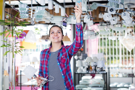 appliances: Woman in shop of home appliances choosing modern and stylish pendant lamp for home