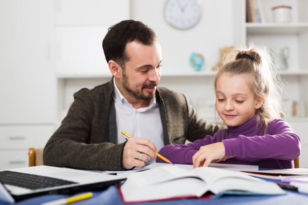 Father helping his child to do homework at home