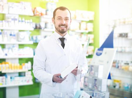 Positive male pharmacist offering right drug in pharmacy