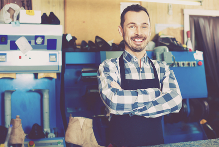 boastful: Young diligent smiling male worker demonstrating workplace and tools in shoe repair workshop