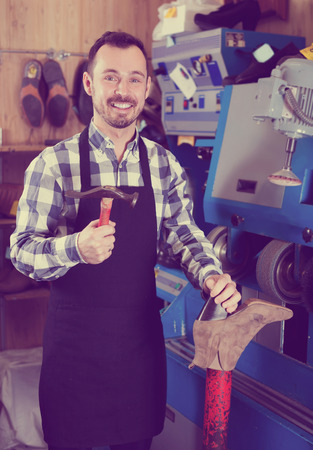 specialized job: Positive man worker using tools for fixing in boots repair workshop