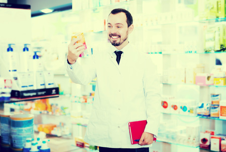 store shelf: Young positive male pharmacist noting assortment of drugs in pharmacy