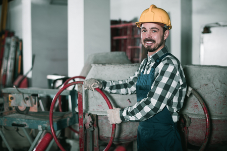 Young male worker starting to work with cement mixer at workshop