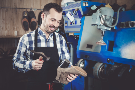 specialized job: Portrait of adult worker repairing shoe in specialized workshop