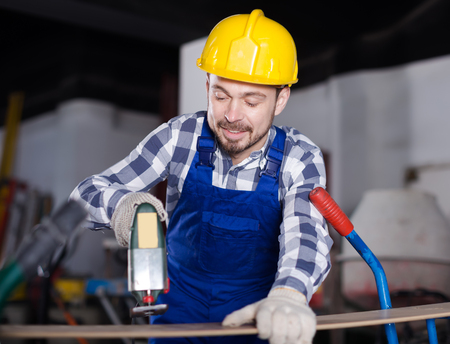 Glad male worker starting to work with power jigsaw at workshop