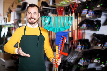 Portrait man seller displaying various items in garden equipment shop