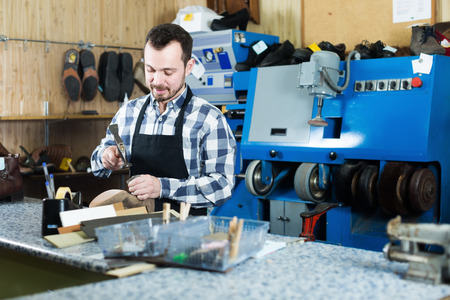 specialized job: Smiling man worker using tools for fixing in shoe repair workshop