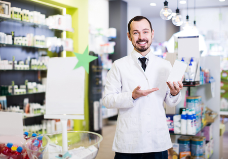 Cheerful male pharmacist offering reliable drugs in drugstore Stock Photo