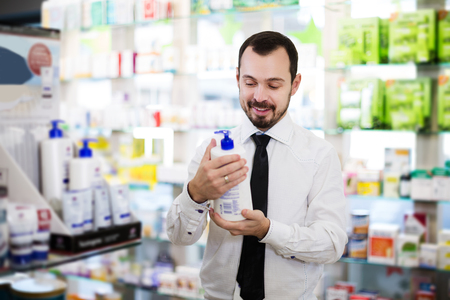 Happy adult customer searching for reliable drug in pharmacy
