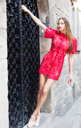 cheeful: portrait of sexy young positive british woman in red dress walking in the old city Stock Photo