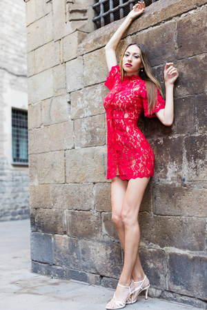 cheeful: portrait of sexy young smiling belorusian woman in red dress walking in the old city