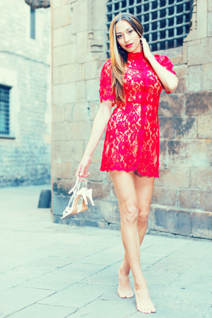 cheeful: portrait of young cheeful french female in sexually red gown with pumps in hands standing in town
