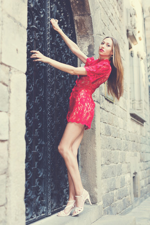 cheeful: portrait of sexy young positive swedish  woman in red dress walking in the old city Stock Photo