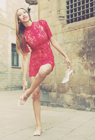 portrait of young slim american female in sexually red gown unshoe pumps  in the street Stock Photo