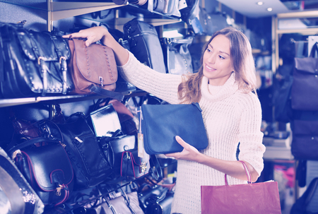 clothing store: Cheerful female choosing bag among assortment in store