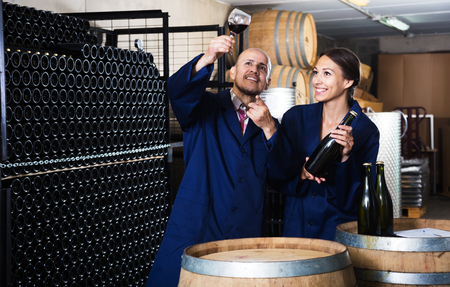 Glad man and women coworkers looking at wine in glass standing in wine cellar. Focus on man Stok Fotoğraf - 82434506