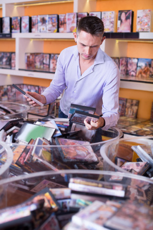 adult sex: Portrait of adult man buying erotic films in a sex shop