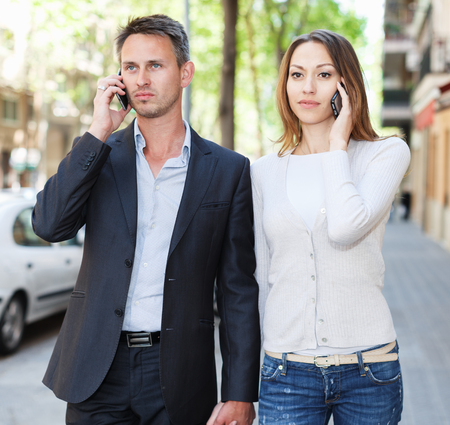 disagreeing: Young couple strolling together and ignoring each other speaking on phones