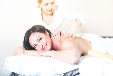 cheerfulness: Glad young masseuse massaging shoulders and neck of adult woman in beauty parlor