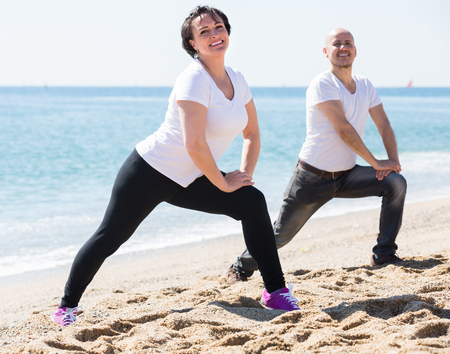 Cheerful smiling mature couple making yoga exercises on the sandy beach. Focus on woman