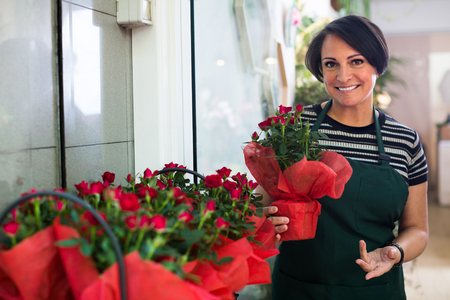 cheerful woman florist holding a pot with a flower in the gardening boutique