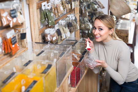 store shelf: Joyful smiling young blond woman choosing spices sold by weight in organic shop