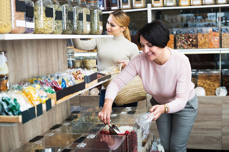 store shelf: Cheerful young blond and adult brunette women choosing dried herbs sold by weight in organic shop
