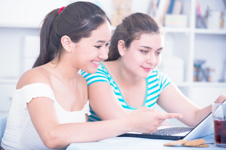 Two girls having fun together at home and watching movie on laptop