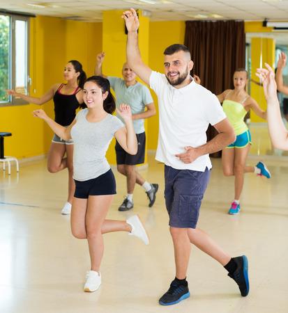 Young dancing couples enjoying active swing in modern studio