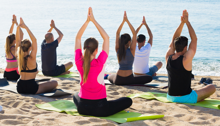 Group of people practicing yoga in lotus positions on beach and looking at smooth sea