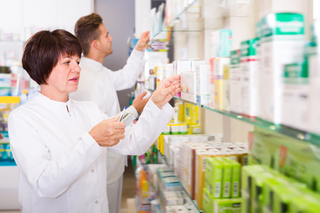 store shelf: Portrait of two ordinary adult pharmacists working in modern farmacy