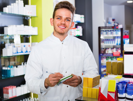 clothing store: Smiling  glad male pharmacist wearing white coat standing among shelves in drug store